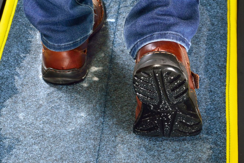 SaniStride customer adds shoe sanitizer to shoe disinfecting mat diminishing the spread of germs