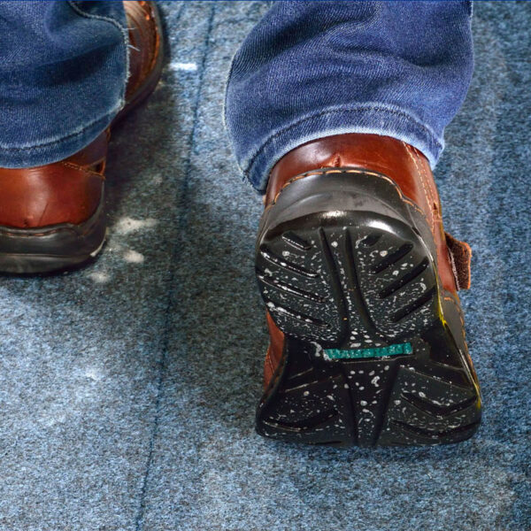 SaniStride customer adds shoe disinfectant to shoe sanitizing doormat diminishing the spread of germs
